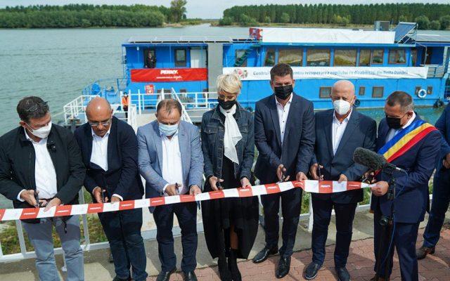 Penibil. Șapte oameni, în frunte cu ministrul Raluca Turcan, înghesuiți să taie o panglică la inaugurarea unui centru itinerant pentru copiii cu dizabilități din Delta Dunării
